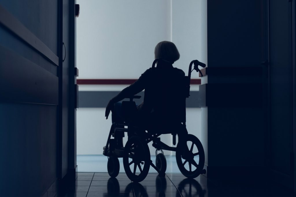 Woman sitting in wheelchair dark hallway